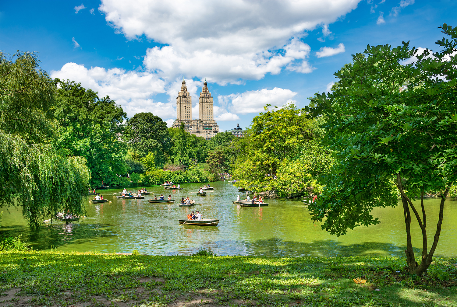 Summer scene in NYC Central Park with boaters on lake.